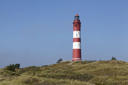 pharos: The red-white ringed lighthouse Amrum is located west of Wittduen and is part of the community Nebel (Germany, Schleswig-Holstein, North Frisia).