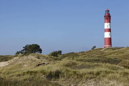 ringed: The red-white ringed lighthouse Amrum is built on top of a sand dune and is part of the community Nebel (Germany, Isle of Amrum, Schleswig-Holstein, North Frisia). Stock Photo