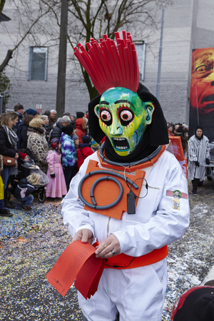 vernacular: A fully costumed carnival activist walks through the city during the carnival procession (cortege) of the Carnivel at Basel 2016 (Basle - Switzerland) on February 15, 2016. Some unidentified visitors watching the procession from the edge of the road. Editorial