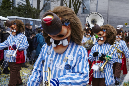 procession: Some fully costumed carnival activists walk through the city during the carnival procession (cortege) of the Carnivel at Basel 2016 (Basle - Switzerland) on February 15, 2016. Some unidentified visitors watching the procession from the edge of the road.