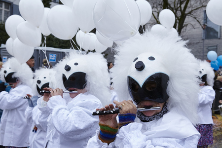 vernacular: Some fully costumed carnival activists walk through the city during the carnival procession (cortege) of the Carnivel at Basel 2016 (Basle - Switzerland) on February 15, 2016. Some unidentified visitors watching the procession from the edge of the road.
