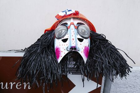 vernacular: A face mask lays on a traffic sign at the Carnivel at Basel 2016 (Basle - Switzerland) on February 15, 2016.
