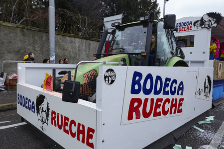 waggon: A carnival waggon drives through the city during the carnival procession (cortege) of the Carnivel at Basel 2016 (Basle - Switzerland) on February 15, 2016. Some unidentified visitors watching the procession from the edge of the road.