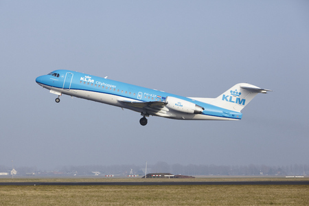 airborn: A Fokker 70 of KLM Cityhopper takes off at Amsterdam Airport Schiphol (The Netherlands, AMS) on March 11, 2016. The name of the runway is Polderbaan. Editorial