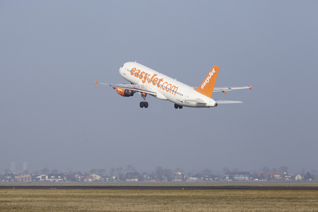 airborn: An Airbus A320-214 of EasyJet takes off at Amsterdam Airport Schiphol (The Netherlands, AMS) on March 11, 2016. The name of the runway is Polderbaan. Editorial