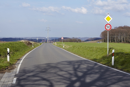 preference: Traffic signs calls attention to a sharp turn into a country road under a blue sky. Stock Photo