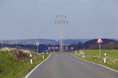 Traffic signs calls attention to a sharp turn into a country road under a blue sky. Stock Photo