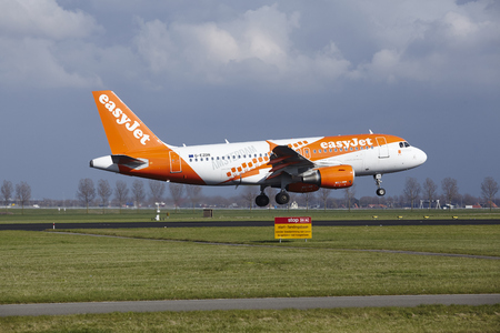 The Easyjet (Amsterdam livery) Airbus A319 with identification G-EZDN lands at Amsterdam Airport Schiphol (The Netherlands, AMS), Polderbaan on April 8, 2016.