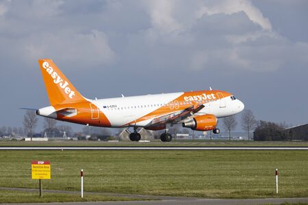 polderbaan: The Easyjet Airbus A319-111 with identification G-EZEV lands at Amsterdam Airport Schiphol (The Netherlands, AMS), Polderbaan on April 8, 2016.