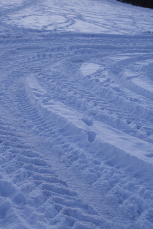 skid: Some skid marks lead into a snowscape at the point of the blue hour in the evening.