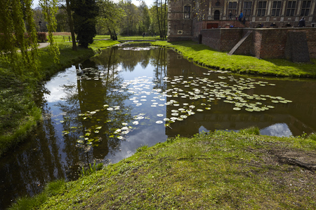 The moated castle Raesfeld (Germany, Northrhine Westphalia, County Borken) reflects in the water of the moat. Stock Photo