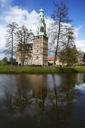 The overall view of moated castle Raesfeld (County Borken, Northrhine-Westphalia, Germany) reflects into the water surface of the moat on April 2017, 17.