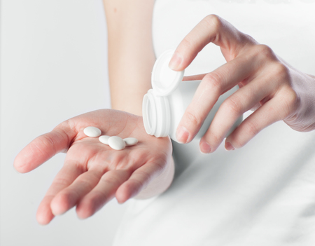 heal sickness: hand holding white pills on gray background