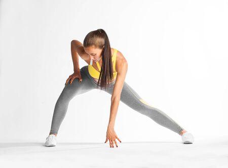 beautiful brunette doing step aerobics on white background