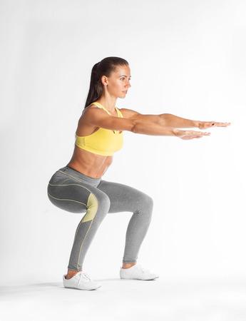 squat: sportswoman squating isolated on white background