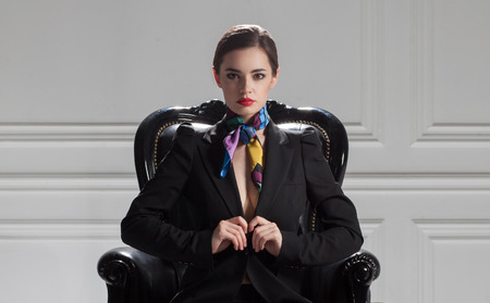 chairman: fashion caucasian model in black suit sitting in chair