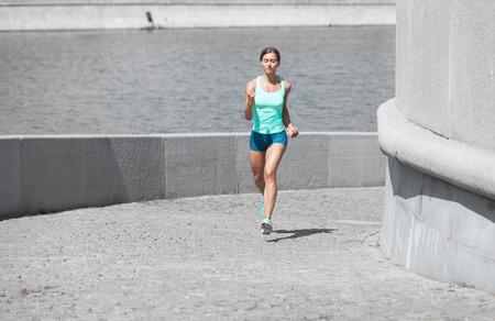 uphill: caucasain sportswoman jogging uphill on the stone road