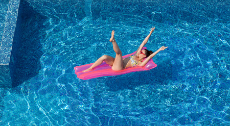 yahoo: one sexy woman doing yahoo gesture on swimming mattress in pool