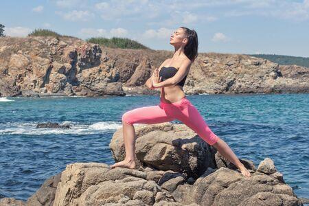 yoga pants: young beautiful fit brunette doing yoga on sea rocky coastline