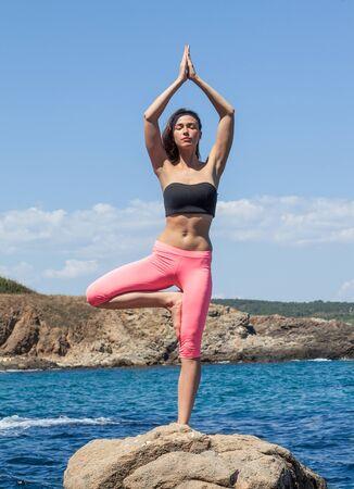young beautiful brunette woman doing yoga outdoor, on coastline