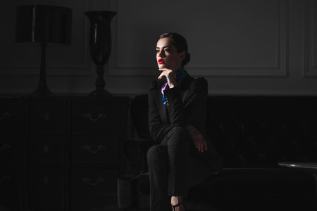 beautiful caucasian woman in black strict suit sitting on sofa