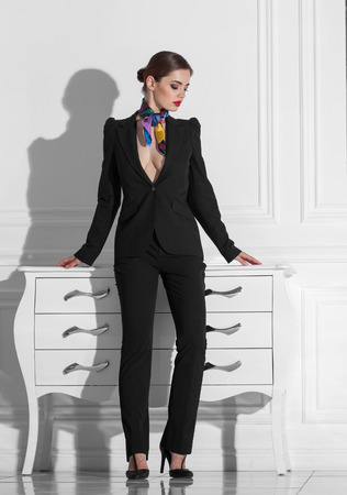 charming girl: fashionable woman in black suit staying in white minimalistic interior