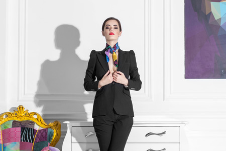 supercilious: fashionable woman in black suit staying in white minimalistic interior