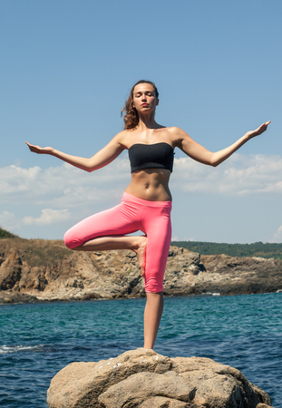 brunette hispanic woman staying in yoga pose on the stone on the sea coast