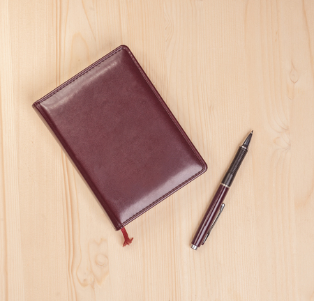 authorship: top view photo of closed notepad with pen on wooden desk