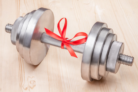 sport equipment: photo of steel dumbbell tied red gift ribbon on wooden surface