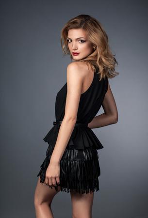 Photo of young blonde slim female model in black dress on gray bakcogrund