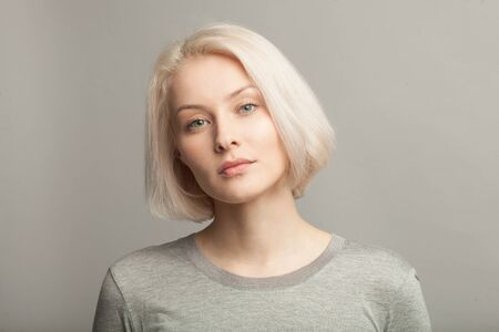 Photo close up portrait of young attractive blonde caucasian woman in gray t-shirt on gray bakcground