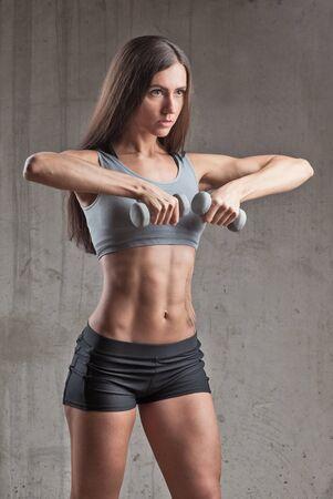young beautiful brunette muscular woman near concrete stone wall