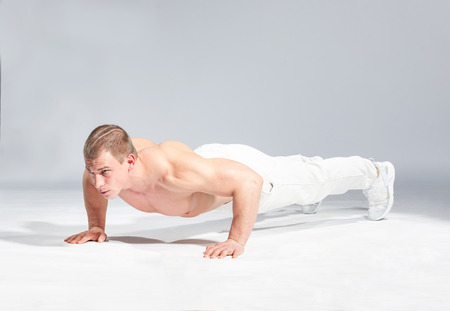 anaerobic: young caucasian bodybuilder doing exercise on studio gray bacground Stock Photo