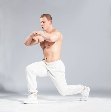 seins nus: young caucasian bodybuilder doing exercise on studio gray bacground Banque d'images
