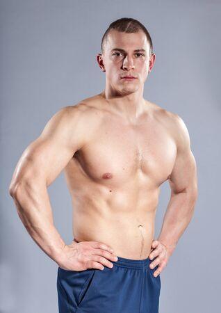 seins nus: young caucasian bodybuilder on blue background Banque d'images