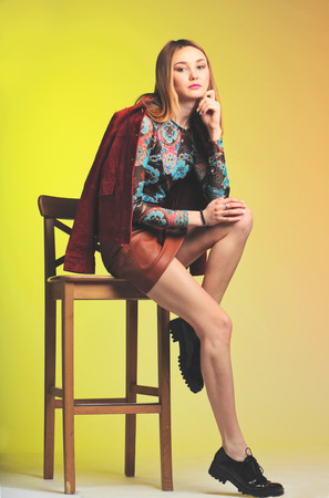 colorfully: young fashion model sit on chair on colorfully background