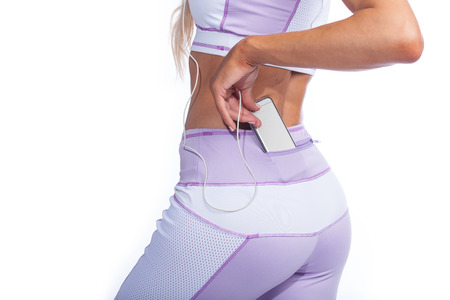 bare waist: woman in pink sportswear with music player in pocket back view isolated Stock Photo