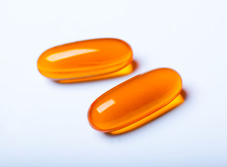 pharmaceutic: macro photo of two orange transparent pills isolated on white background
