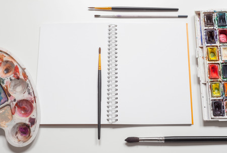 boarder: open blank sketchbook mockup with paints and brushes on white table