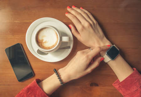 lunch table: female hands using smart watch with blank screen on wooden table with smartphone and coffee, top view