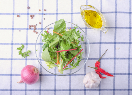 surrounded: dish of salad surrounded ingredients, olive oil, pepper, garlic, onion on squared print cloth table, top view Stock Photo