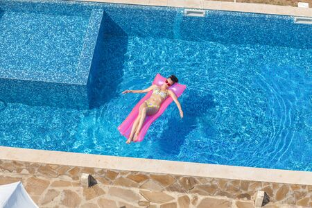 young girl bath: young sexy brunette woman have a sun bath on pink inflatable mattress in swimming pool