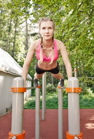 push ups: young female sportswoman in sportswear doing push ups on sports bars, outdoor nature gym Stock Photo