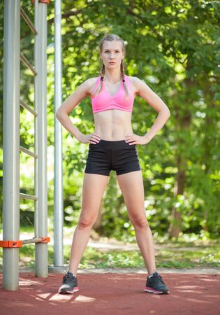 slim women: young white female sportswoman in sportswear on outdoor nature sports ground, summer