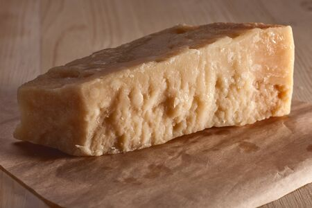 parmezan: italian cheese parmigiano with rich texture on wooden table