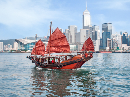 Hong Kong harbour with traditional red-sail Junk boat on city skyscrapers urban background Stock Photo