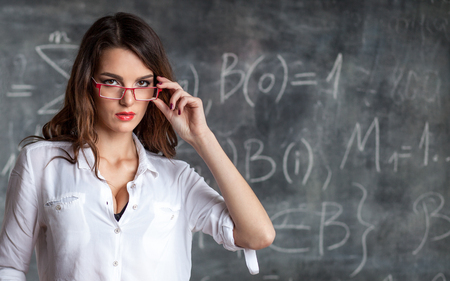young smart attractive female scientist in glasses near blackboard with math calculations Stock fotó