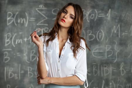 Mujer hermosa morena atractiva joven cerca de la pizarra con cálculos matemáticos