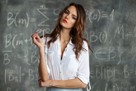 young sexy gorgeous brunette woman near blackboard with maths calculations